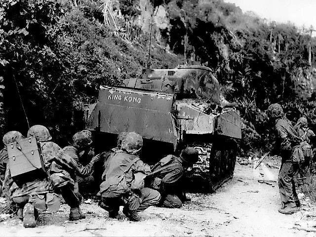 US Marines advancing under the cover of a M4 Sherman medium tank northern Saipan Mariana Islands 8 July 1944.
