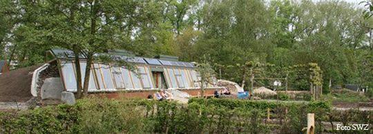 Een earthship in Zwolle, opgebouwd uit een glazen pui, autobanden in de muren een aarde wal aan de achterzijde.