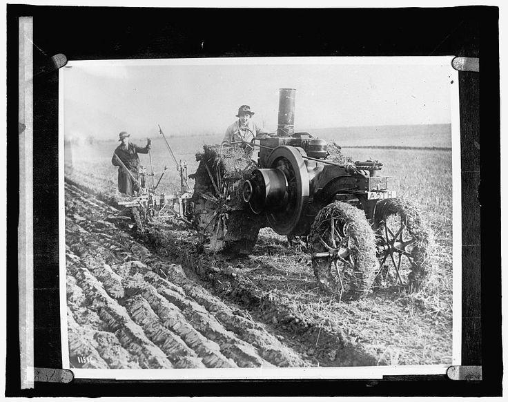 OLD FARM EQUIPMENT - WIFE DRIVES STEAM POWERED TRACTOR THROUGH MUDDY FARM FIELD A FARMER GUIDES SOIL TURNING PLOW