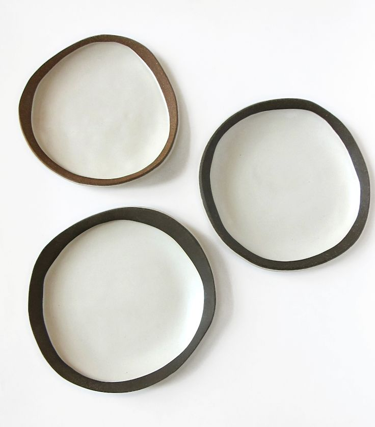 "Shallow dishes made by layering brown stoneware on top of white. The inside  is glazed with a food-safe satin white, and the rim and exterior are left  unglazed.  Red-brown edge dish: approximately 8"" in diameter, $55  Dark brown edge dishes: approximately 8.5"" in diameter, $65"