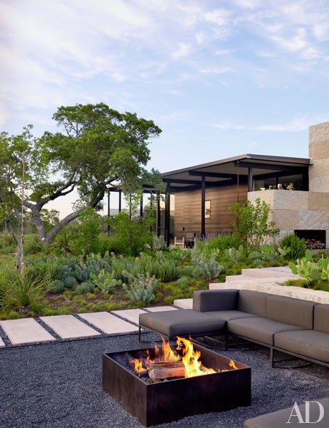 A Gloster sectional sofa provides seating around the fire pit | archdigest.comc