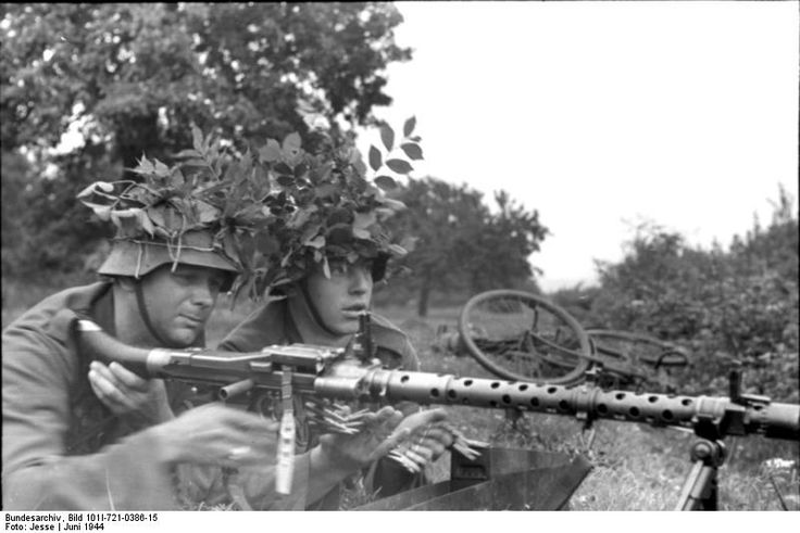 Two German soldiers with camouflaged helmets with a MG34 machine gun, France, Jun 1944