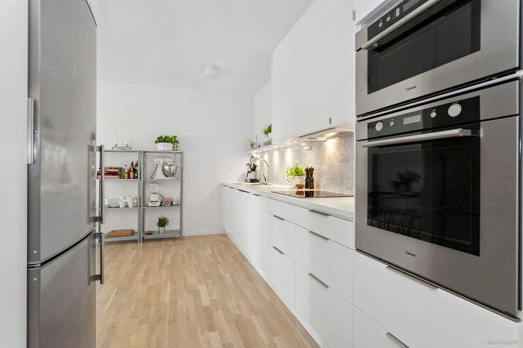 Kök med vita luckor och stilrena handtag. Arbetsytorna är rejält tilltagna med gott om förvaring och köket har rostfria vitvaror från Cylinda | Ballingslöv