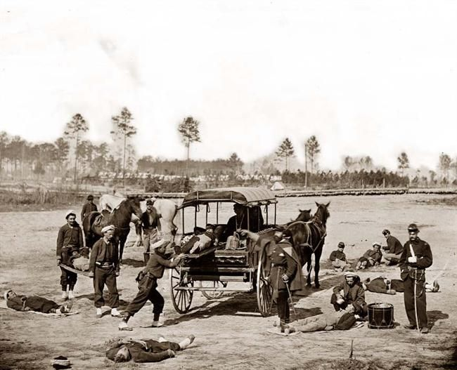 This is a stunning photograph from 1862. The image shows a Civil War Ambulance crew removing the wounded from a battlefiled. It shows a horse-drawn ambulance, and the Zouave uniforms of this unit.:
