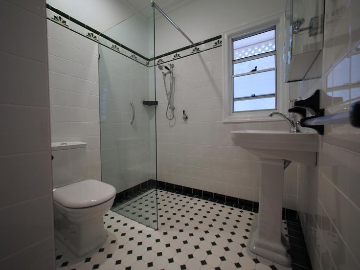 Wide angle toilet suite, shower and pedestal basin.  Black, white and green mosaic floor tiles.