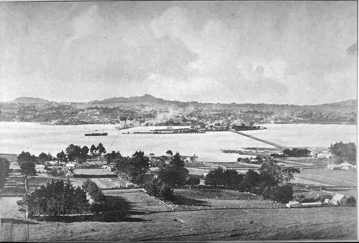 1907. Looking north from Mangere Mountain over Mangere and the Manukau Harbour towards Onehunga with One Tree Hill (right background) and Mount Eden (left background) and Mangere Bridge (centre right) with Church Road (diagonally right to centre) and Onehunga Wharf (centre left). Sir George Grey Special Collections, Auckland Libraries, 7-A1822.