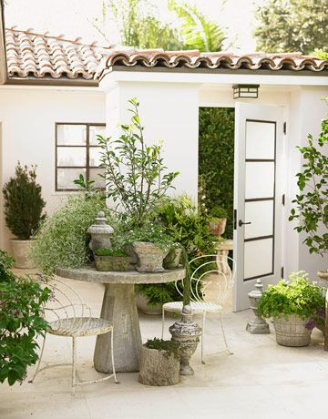 A Secret Garden  The front door of this oceanfront Los Angeles house opens to a surprising open-air courtyard. Designer Chris Barrett clustered plants in antique pots on a concrete table from Inner Gardens.
