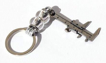 """Porte-clés avec un pied à coulisse orné de deux rondelles de verre transparentes : """"Le pied à coulisse"""""""