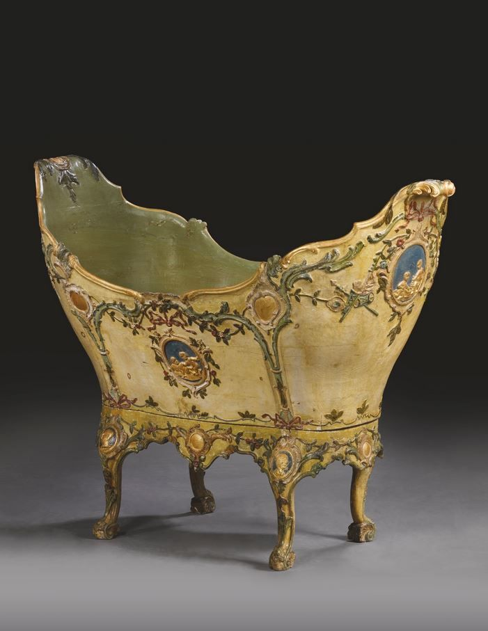An Italian yellow, pale green, polychrome lacquered and parcel-gilt carved wooden cradle, Venice, circa 1770.