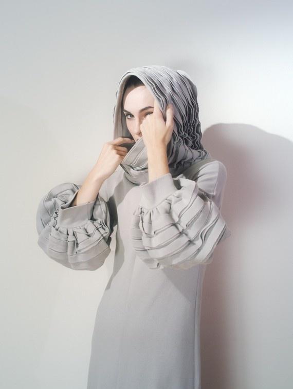 Sculptural dress with hood.
