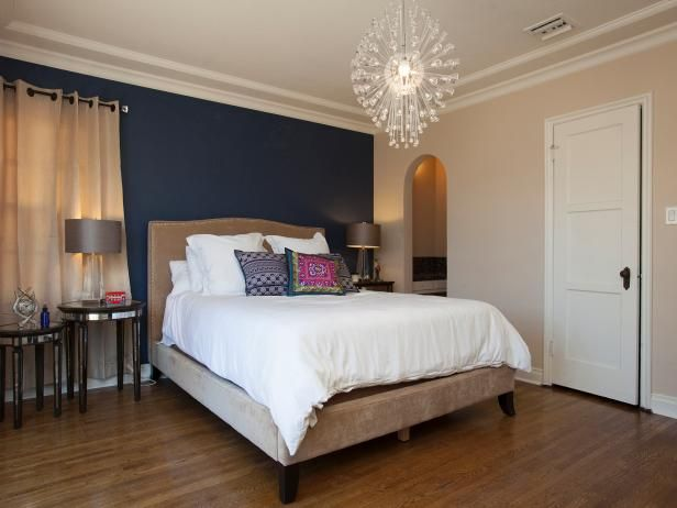 HGTV loves the combination of a neutral color palette against a navy blue accent wall in this contemporary bedroom.