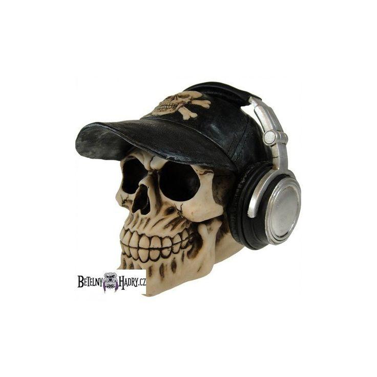 Pokladnička ve tvaru rozesmáté  lebky s kšiltovkou a sluchátky.
