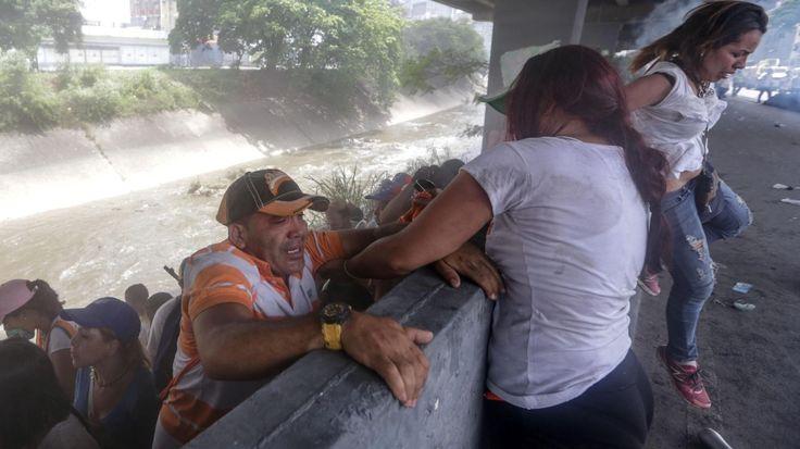 REPRESION EN CARACAS. Una mujer ayuda a un hombre a subir de una pendiente a la orilla de un canal durante una protesta en contra del Gobierno venezolano de Nicolás Maduro, el miércoles 19 de abril de 2017, en Caracas, Venezuela. Miles de opositores...