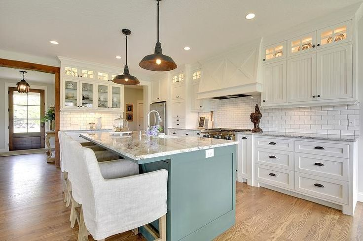 A pair of black vintage barn pendants hang over a green blue kitchen island topped with gray and white granite fitted with a sink lined with linen slipcovered counter stools atop a white oak floor.