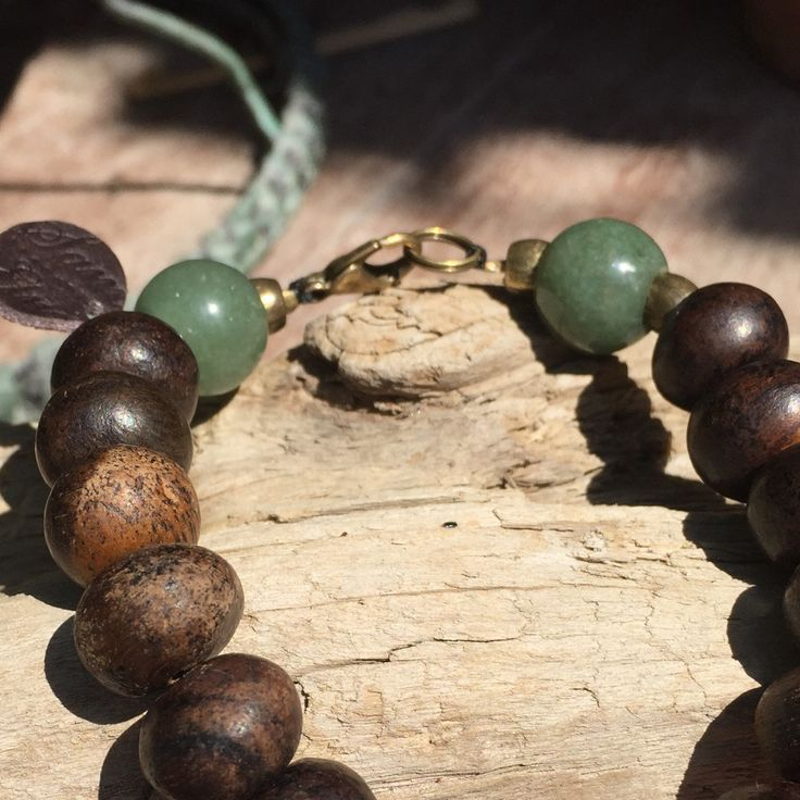 ZenJad Bracelet réalisé sur un fil poissé orné de perles de bois et de deux perles de Jade. Fermoir laiton. Taille 22,5cm Le Jade associé au chakra du Coeur intensifie les sentiments d'Amour. C'est une Pierre protectrice qui attire la chance et l'Amitié.