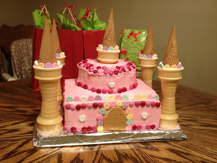Easy to assemble pink princess castle cake (just the picture. Two square cakes, two smaller circles, graham cracker door, sugar cones and cake cones for the towers, candy for decoration.) my 2 year old loved it!