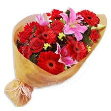 One sided bouquet of mixed red and pink flowers with golden color paper packing.