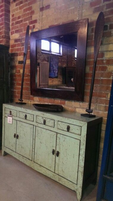 """Another stunning colour. Coming from 1920s Shanxi, China this solid poplar teal console is speckled with age. It has four drawers and tons of storage space in the cabinets below. 35.5"""" H 60"""" W 16.5"""" D. -$1395 It is shown with a wood framed mirror 39"""" SQ -225$ a hand carved plate -$65 and a set of mounted solid wood oars - $250"""