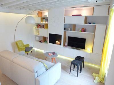 Dans la partie salon, le mur comprend une composition de rangements et une cheminée intégrée au bio-éthanol.