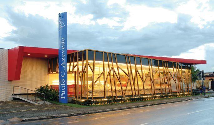 A fachada envidraçada possui esquadrias metálicas. O desenho irregular confere personalidade à edificação