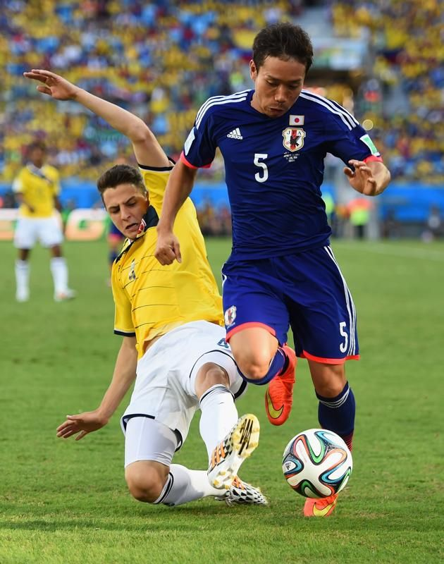 Santiago Arias of Colombia tackles Yuto Nagatomo of Japan during the 2014 FIFA World Cup Brazil Group C match between Japan and Colombia at Arena Pantanal on June 24, 2014 in Cuiaba, Brazil.