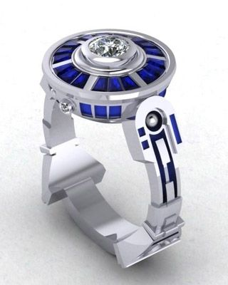 Paul Bierker is a master of custom made rings and jewelry. Looking through  this guy's work It's clear he does some amazing things, but I personally  think that these Star Wars inspired R2-D2 wedding rings are his  masterpiece. I don't think you will find a better R2-D2 themed wedding ring  or bands. It's pretty impressive work, don't you think?