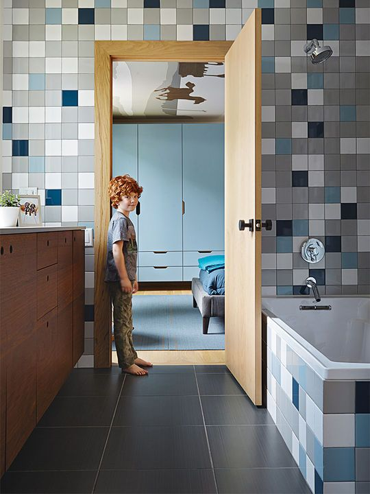Rock stands in the doorway to the boys' bathroom, which is lined with semi-gloss Modern Dimensions tiles from Daltile.