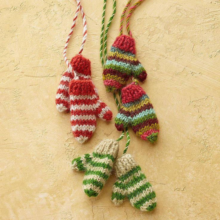 "STRIPED MITTENS ON A STRING, SET OF 3 -- Hand-knit and hand-spun wool mini mittens, striped and strung upon twisted yarn, for decorating or wrapping anything you desire. Made by a women's fair trade cooperative in Nepal. Exclusive. Set of 3. 1/2""W x 2""L, approx. 100"" string."