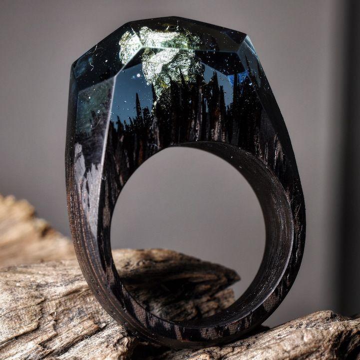 """Essas são peças artesanais feitas pela Secret Wood. Produzidos com madeira fresca, resina e cera de abelha, esses anéis reproduzem """"cápsulas de universo"""", com lagoas, florestas e cachoeiras deslumbrantes prontas para colocar nos dedos. Cada anel é feito sob encomenda e por esse motivo são peças únicas. Eles levam cerca de 5 semanas para finalizarem (...)"""
