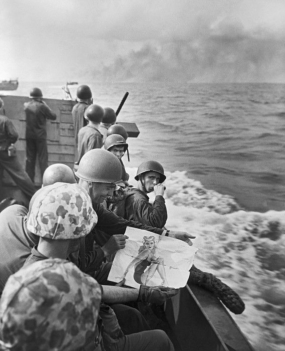 Gilbert Islands, Pacific Ocean 1943. United States Marines on a landing barge share viewing a pin-up girl as they approach the Japanese held island of Tarawa.