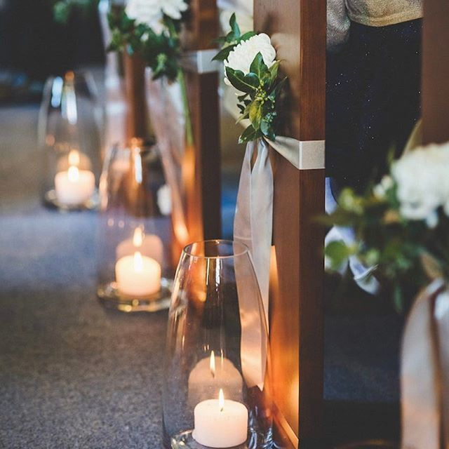 Modern hurricane vases and pillar candles lighting up this sweetly decorated chapel aisle