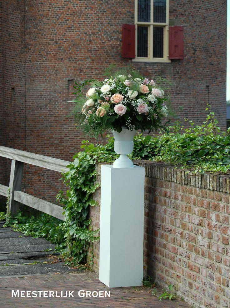 Bruidsdecoratie - bloemstuk op zuil met o.a. rozen in pastel tinten (zacht roze, peach, crème), wit gipskruid, jasmijn ranken, asparagus. www.meesterlijkgroen.nl