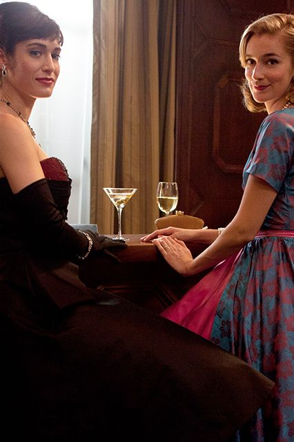 Virginia Johnson and Libby Masters drink up, lady-style. The stark contrast between Johnson's vixen oxblood gown and Masters' demure housewife-inspired dress should clue you into how different these women are. Swooped coifs, fancy frocks, and opulent jewels — click ahead to see how it's done.