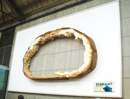 It is an outdoor advertisement poster of Floralp Butter. It has a single focal point as bread which is left only outline. It metaphor a situation that a person ate a slice of bread without outline because there has no butter.