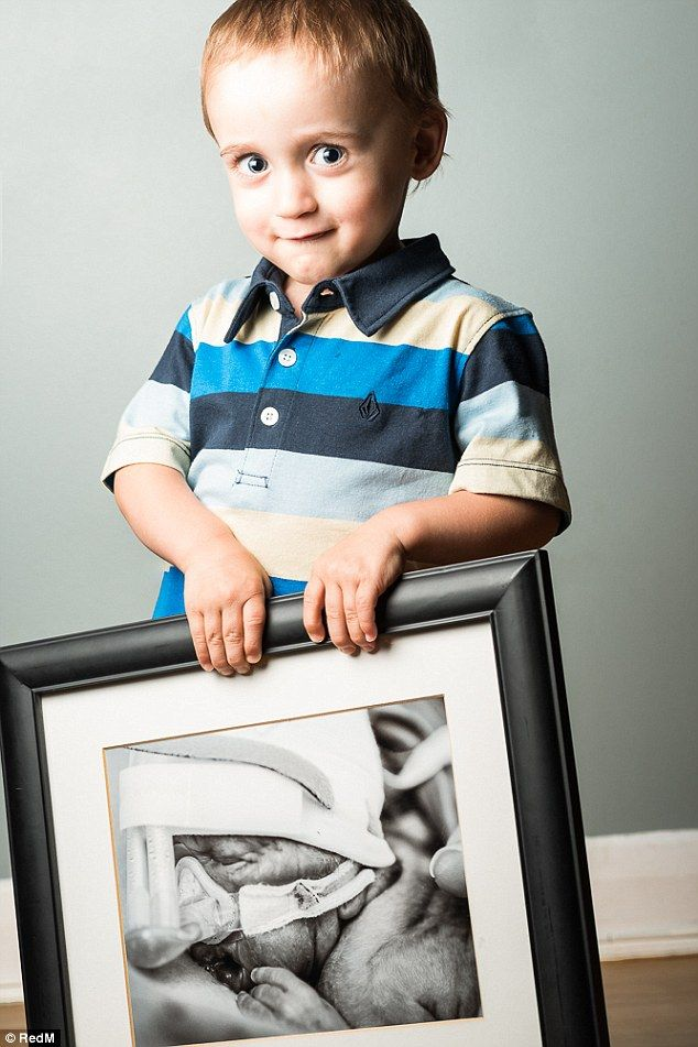 Cheeky Zachary holds a photo of himself fighting for his life, born at 27 weeks