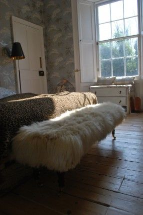 Gorgeous fluffy Ottoman and love the cloudy grey wallpaper, wide windows and shutters.