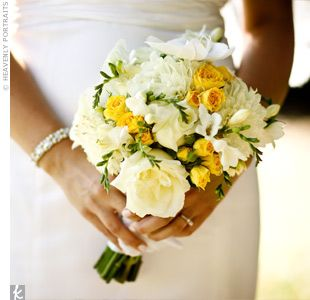 A white, pale yellow and bright gold bouquet filled with orchids, ranunculus, roses, and mums