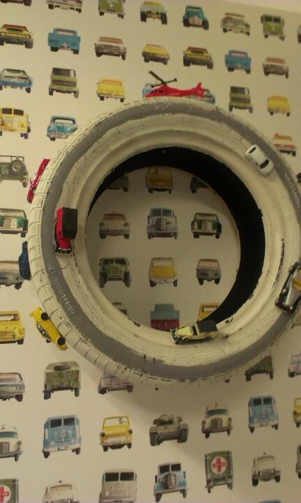 Geschilderde autoband met speelgoedautotjes opgekleefd.