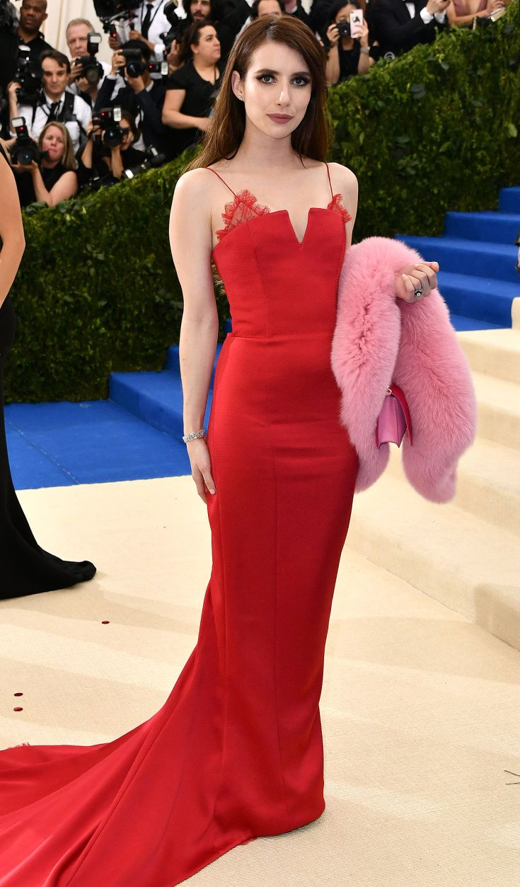 2017 Met Gala: Emma Roberts is wearing a red Diane von Furstenberg gown with lace detailing on the bodice and a pink fur stole. The dress is simple but stunning! The dress fits Emma beautifully!