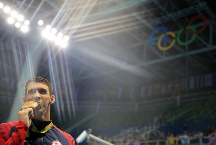 Michael Phelps of the U.S. poses with his gold medal after the men's 4 x 200m freestyle relay at the Rio Olympics August 9, 2016. REUTERS/Dominic Ebenbichler