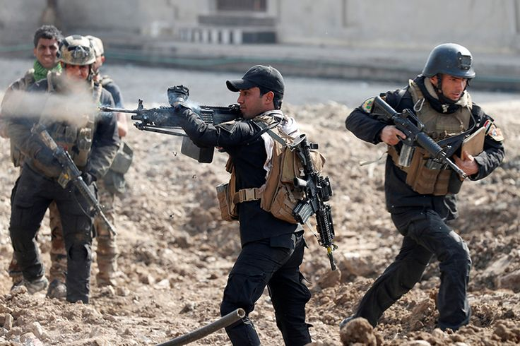 An Iraqi special forces soldier fires as other soldiers run across a street during a battle in Mosul, Iraq, March 1, 2017.  REUTERS/Goran Tomasevic