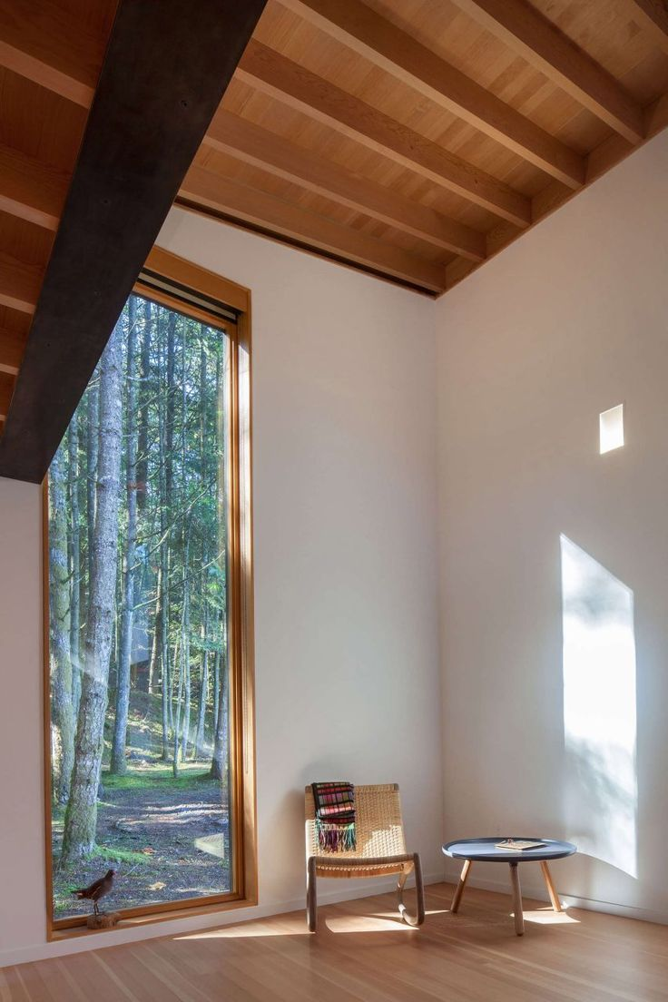 Walls are painted white to add to the airy feel created by large windows and tall ceiling heights of this cabin.