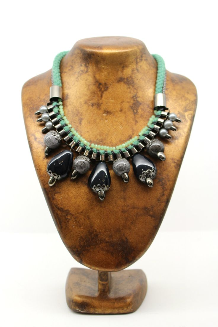 El collar tiene una cuerda trenzada en verde y una cadena cromada. En la parte central salen las cuentas, trenzadas de la cadena, son cuentas de piedra en negro y jaspeado.  Un collar casual para dar un toque diferente a tus looks más sport