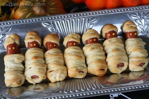Esta sencilla receta para Halloween seguro que les encantará a los peques de la casa. Para crear unas terroríficas momias todo lo que tienes que hacer es envolver unas salchichas en tiras de pasta de hojaldre. Luego hornea según las indicaciones del paquete de la masa de hojaldre. Para hacer los