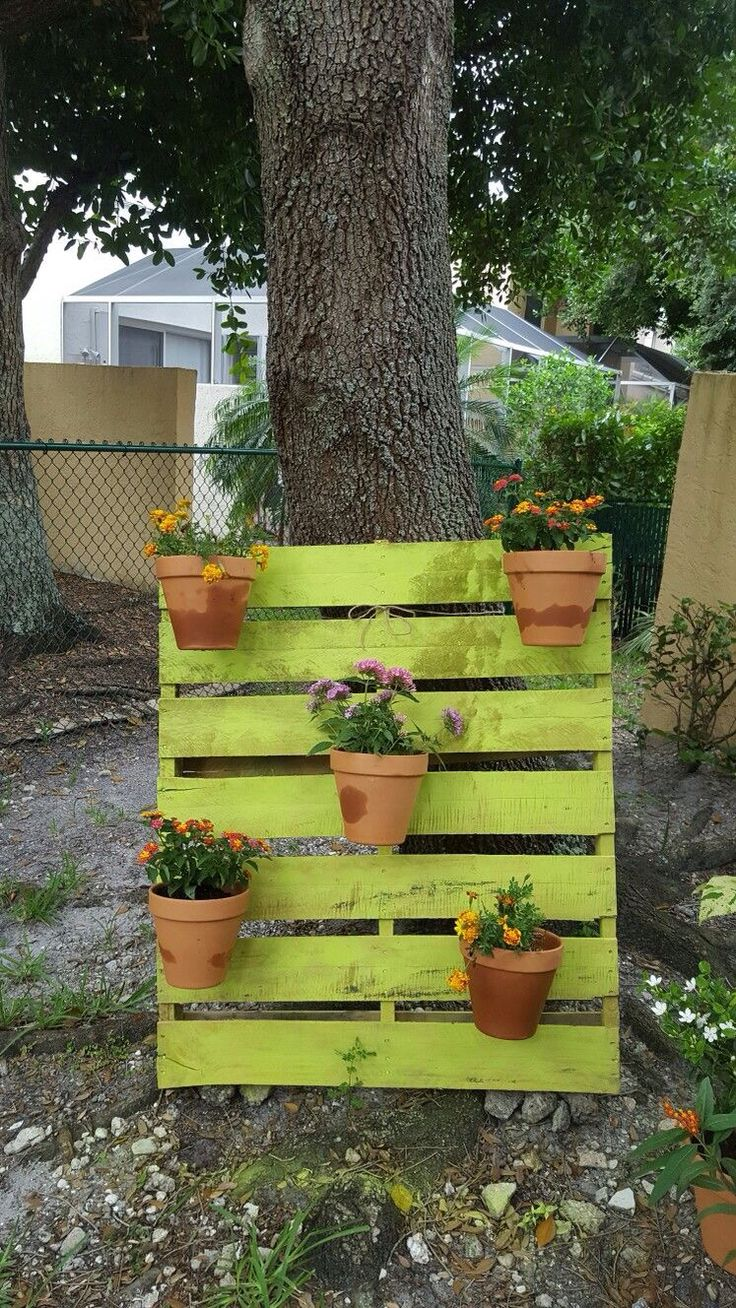 DIY painted pallet garden with flowers in clay pots.An easy vertical garden  design with