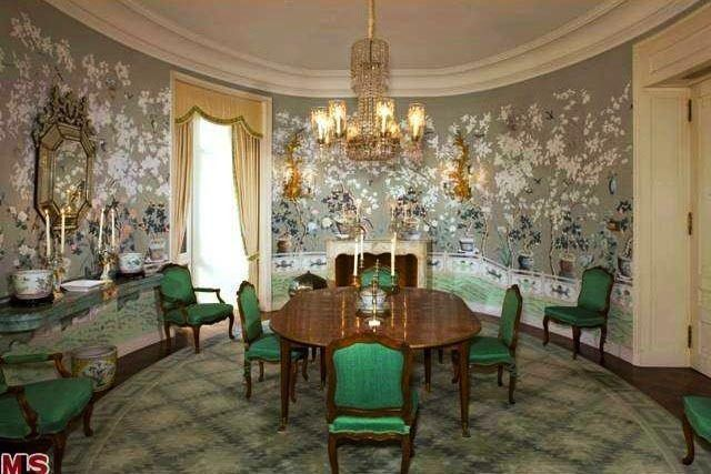 Wallace Neff's 1973 Singleton House in L.A. has an oval dining room with an oval dining table, bright green chairs, a fireplace, curved console table, crown molding, gold drapes with valance and a beautiful floral mural wrapping around the room.