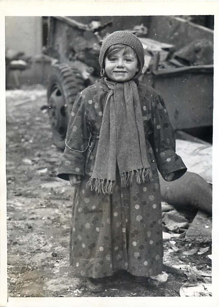 1945-  A little girl beams in Bastogne, Belgium, after her town was relieved from German siege by General Patton's men.