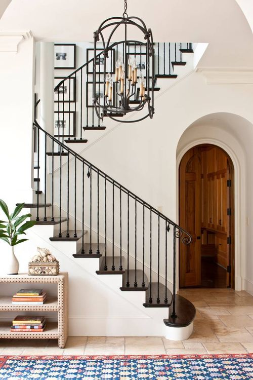 S11 - The photo that inspired the whole style. White walls, black iron stair rails, archways, black rustic chandelier, colorful boho rug