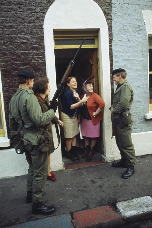 2nd Lieutenant Robin Martin and Rifleman Andy Walker of the 1st Battalion, The Royal Green Jackets, during a friendly conversation with cheerful women in the doorway of their house in in Belfast. This photograph was taken during the first few months of the British Army's deployment to Northern Ireland.