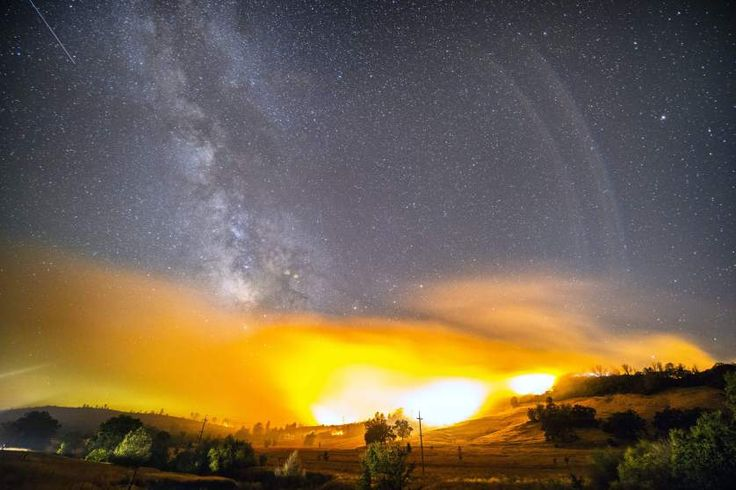 A meteor from the Perseid Meteor shower can be seen in the upper left corner in this long exposure image as the Jerusalem Fire burns in Lake and Napa Counties near the town of Clearlake, Calif., on Aug. 12, 2015.